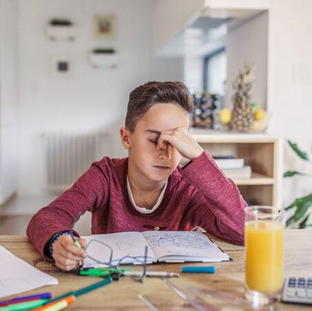 un niño sentado en una mesa estudiando y luciendo realmente estresado