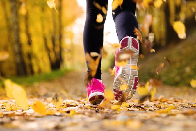 una foto de una persona que huye del espectador en un camino frondoso, ampliada en los pies y la parte inferior de las piernas