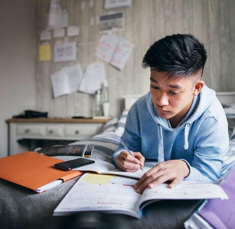 Una foto de un joven asiático estudiando sus notas mientras está acostado en la cama